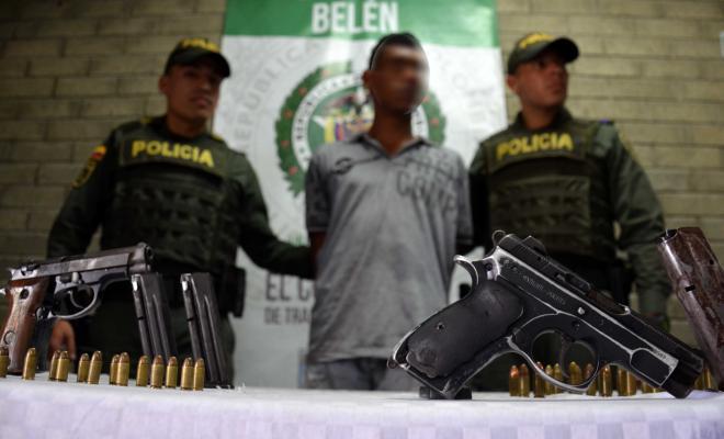 Policía custodian a un capturado en Medellín con dos armas de fuego